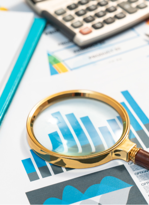 A desk with a calculator and a magnifying glass focusing in a bar graph. Representing how one can benefit from calling a Chicago CFO firm.