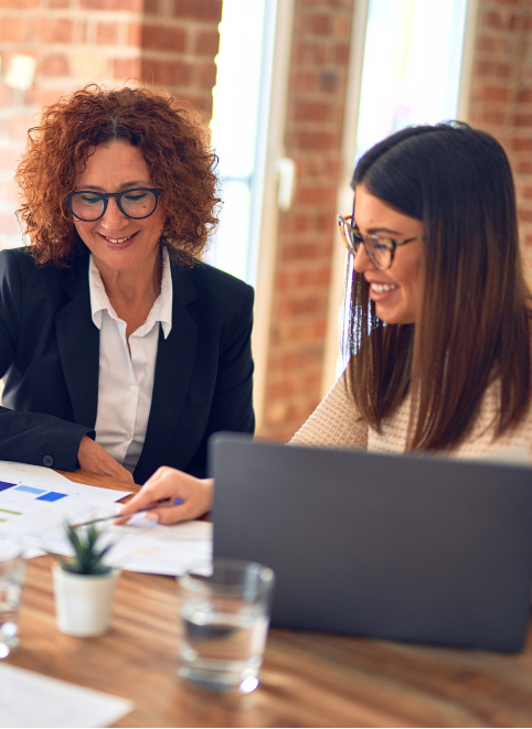 Two business women looking at some paperwork together and smiling, they are sitting a a big desk with a laptop. Representing how one can benefit from calling a CFO firm in Chicago.